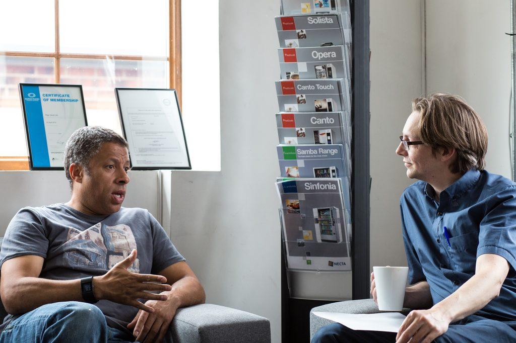 man talking to woman sitting in office