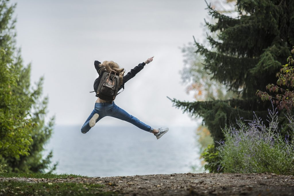 woman jumping in forest with water in the distance