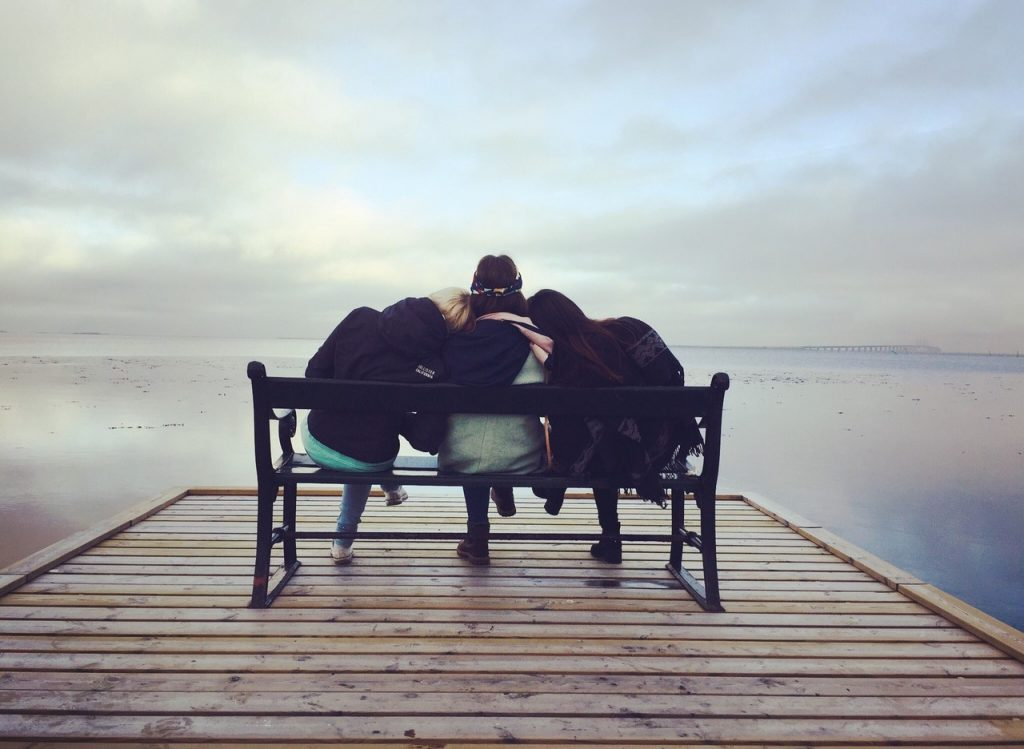 three women leaning on each other on a bench at the end of a dock
