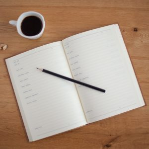 open planner with pencil and coffee