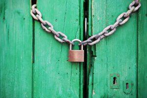 padlocked chain against green wood panels