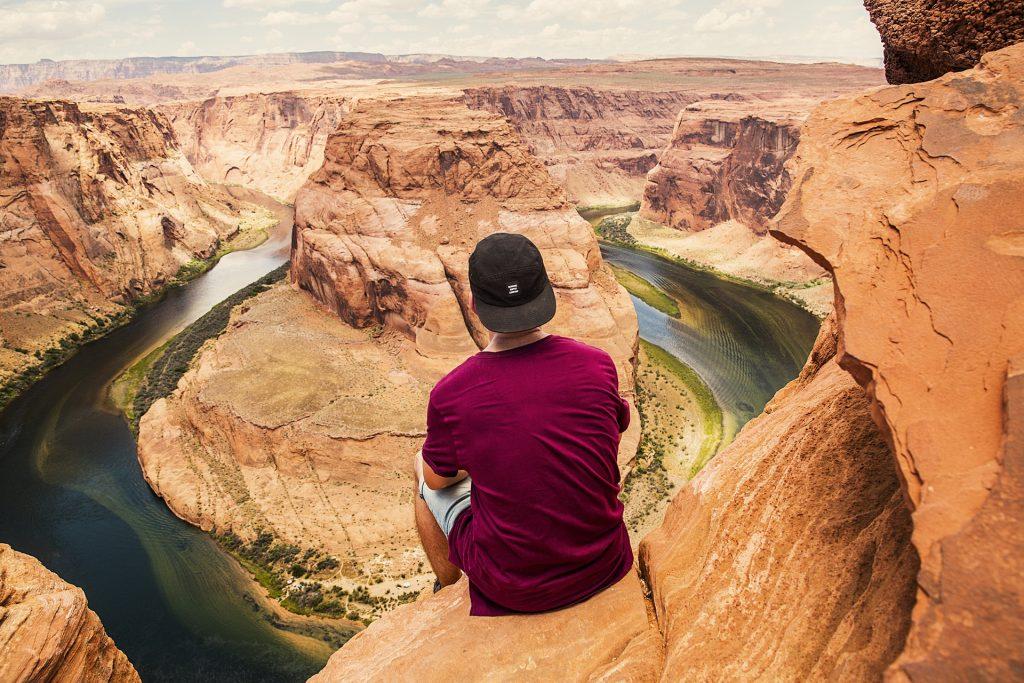 man sitting at edge of canyon