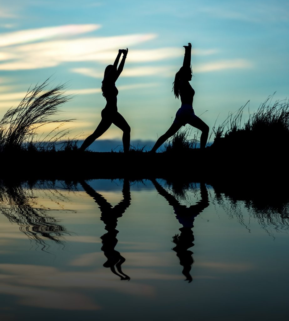 two women doing yoga at sunset by the water