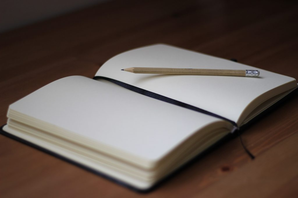 blank notebook open with pencil